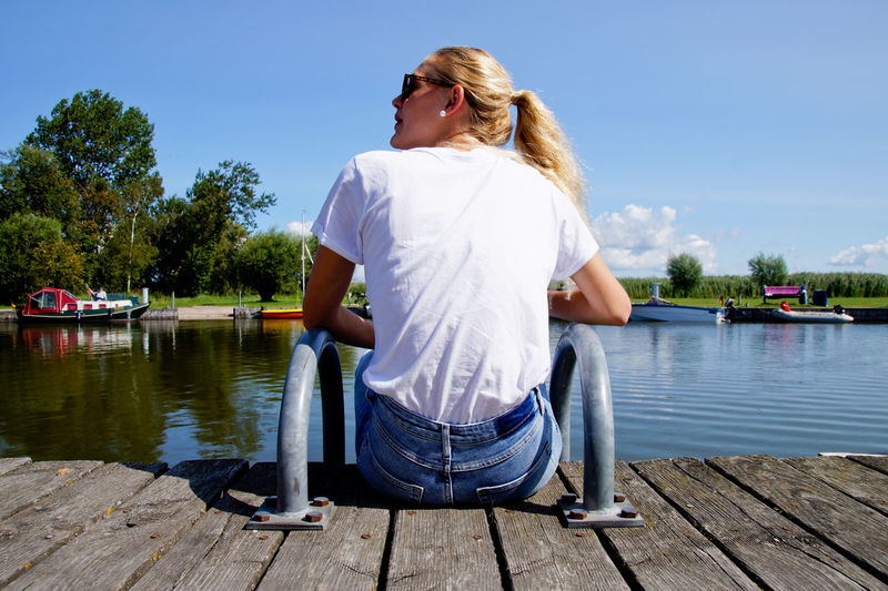 Rear view of young woman sitting on pier over lake