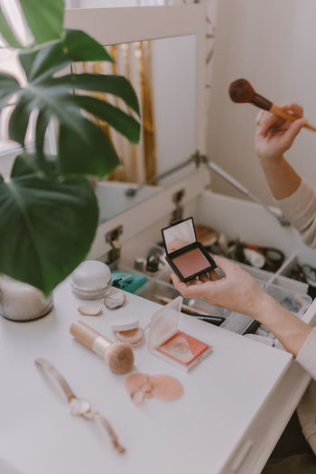 Cropped hand of woman holding make up brush
