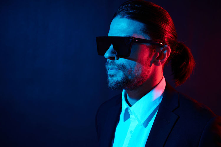 Portrait of young man wearing sunglasses against black background