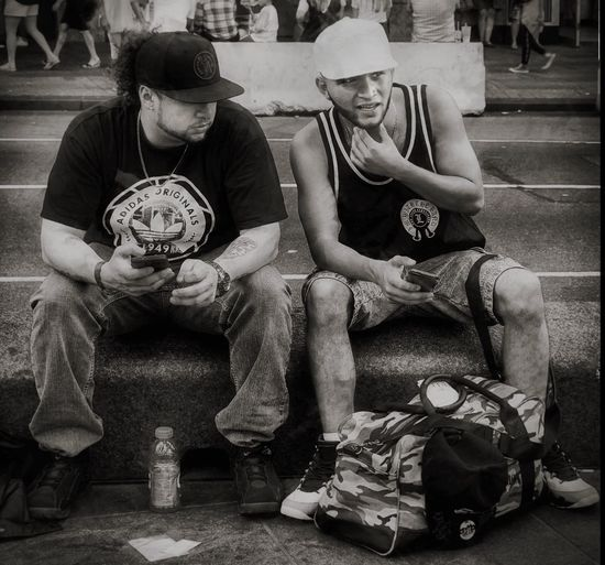 Just Wondering in NYC New York City Sitting Outdoor Enlight App Snapseed Olympus OM-D E-M1 Mark II Faces Hats Black & White NYC Photography NYC BxW Sidewalk View Friendship Males  City