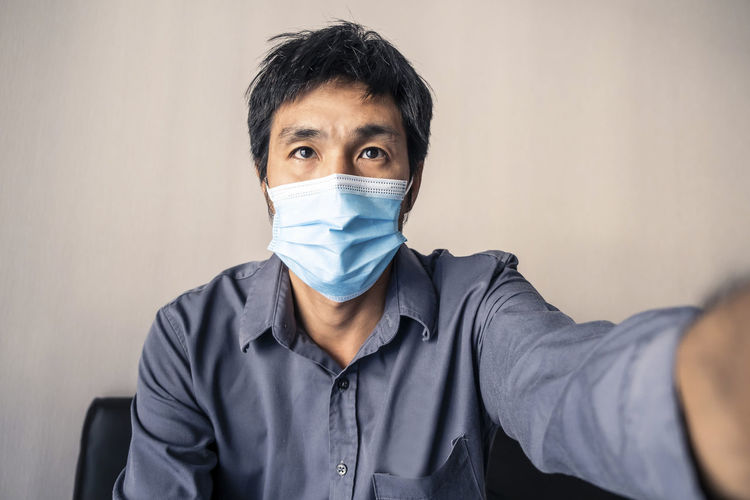 Portrait of man wearing mask sitting against wall
