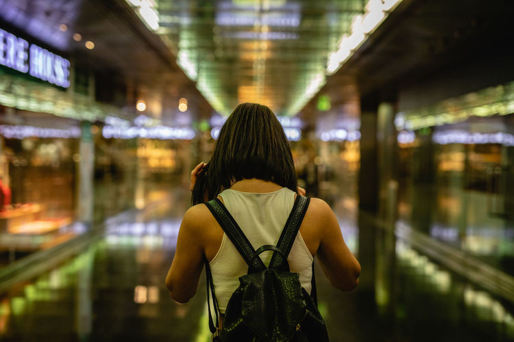 Rear View Of Young Woman Walking In Illuminated Building