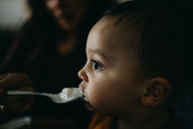 Close-up portrait of cute baby eating