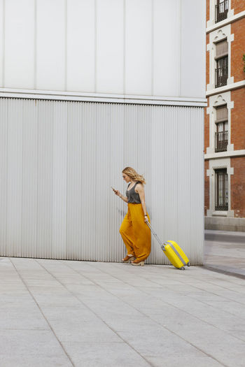 Full length of woman with luggage walking by wall