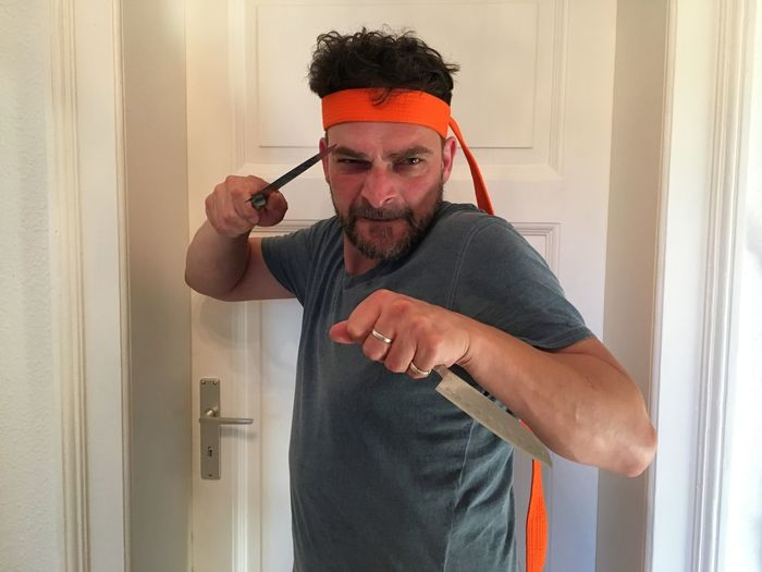 Portrait of playful man holding knives at home