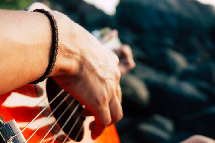 Close-up of person playing guitar
