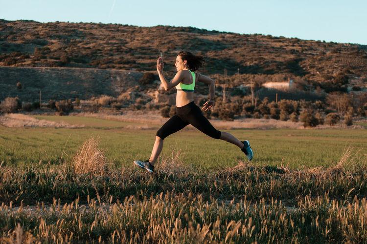 Full length of woman running on field against sky
