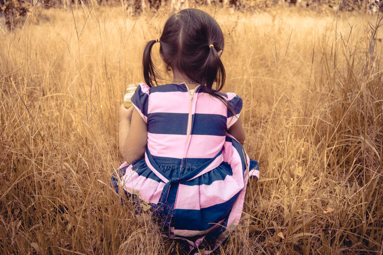 Rear view of girl crouching on grassy field