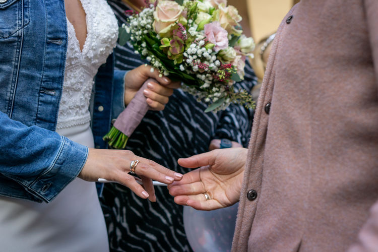 Midsection of couple holding flower bouquet outdors