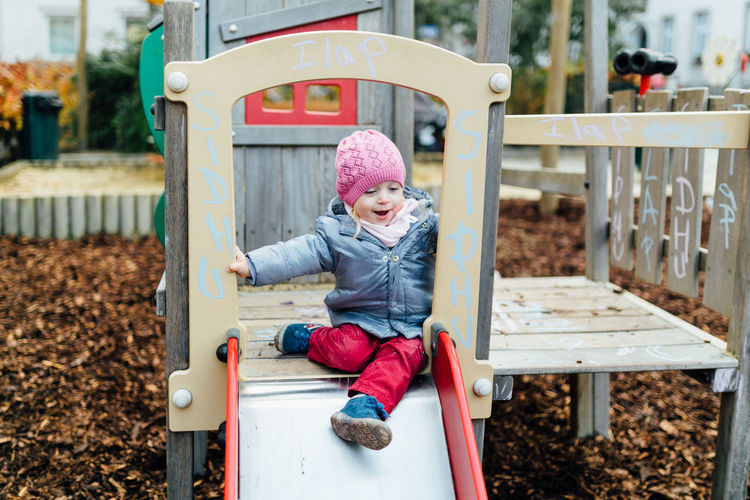 Cute girl wearing warm clothing playing at playground