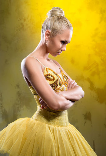 Ballerina wearing costume with arms crossed standing against yellow background