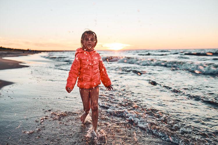 Playful little girl splashing a water towards camera enjoying a free time over sea on a sand beach