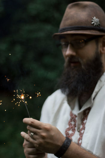 Portrait Of Young Man Burning Sparkler While Standing In Forest