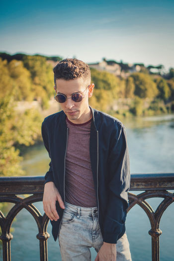 Young man wearing sunglasses standing against railing