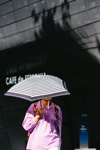 Midsection of woman standing on umbrella