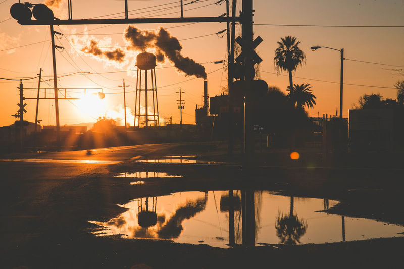 Architecture City Factory Industry No People Outdoors Reflection Silhouette Sky Smoke Sun Sunlight Sunset Urban Water Water Tower