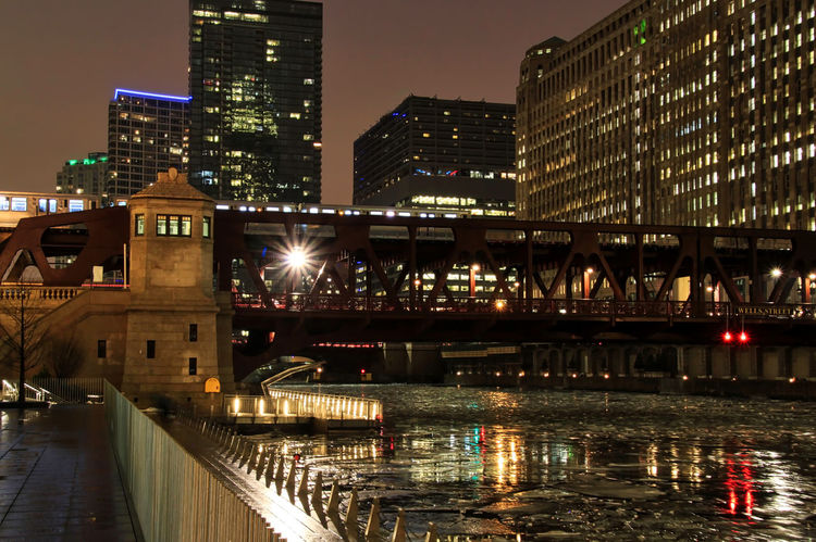 Light beams off of the elevated track as an el train speeds over the Chicago River reflecting illuminated cityscape in winter. Waysofseeing Chicago Chicago River Chicago El Chicago Loop Downtown Chicago Elevated Track Ice Winter Architecture Bridge - Man Made Structure Building Exterior Built Structure City Cityscape Connection Elevated Train Frozen River Icy Illuminated Modern Night No People Outdoors River Sky Skyscraper Transportation Water Shades Of Winter