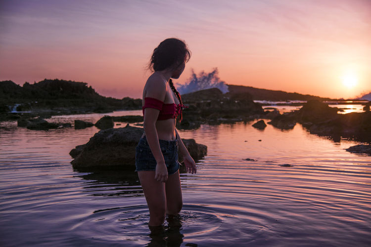 Young woman stands in water at beach at sunrise