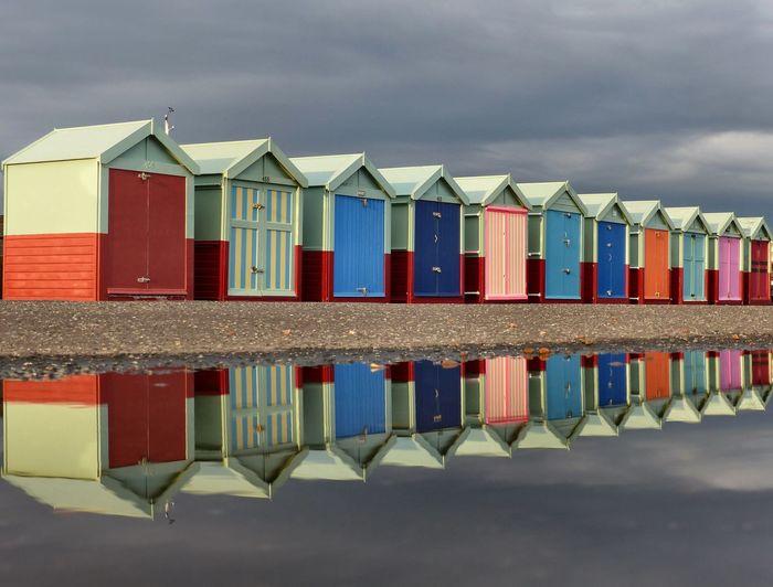 Row of houses on beach against sky