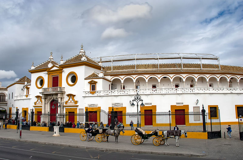 La Maestranza bullring in Seville, Spain Architecture SPAIN Europe Sevilla Seville Andalucía Outdoors Urban Cityscape City Day Built Structure Building Exterior Sky Incidental People Street Building Bullring Bull Ring Bull Fight Bull Fighting In Seville White Building Famous Place Cloud - Sky Road