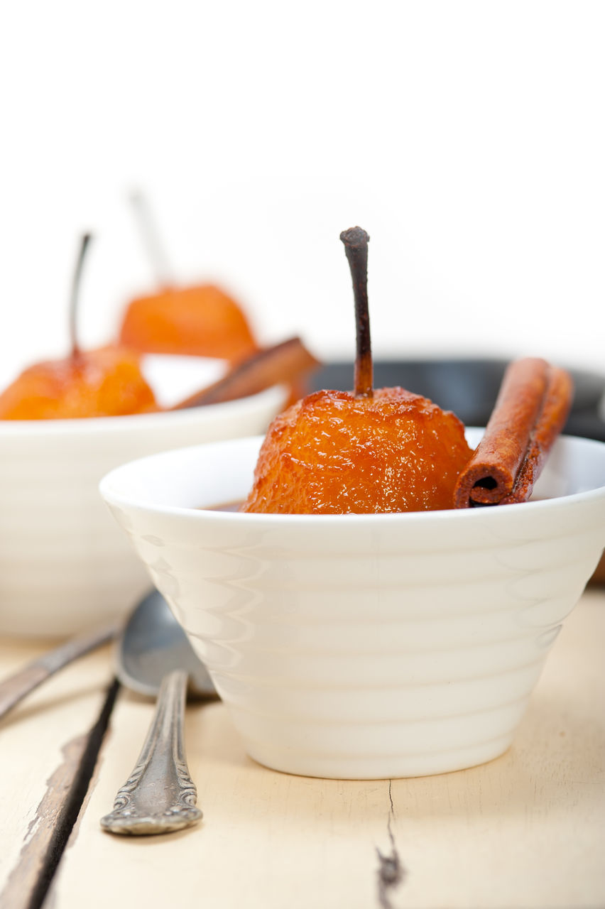 Close-Up Of Poached Pears In Bowls On Table Against White Background