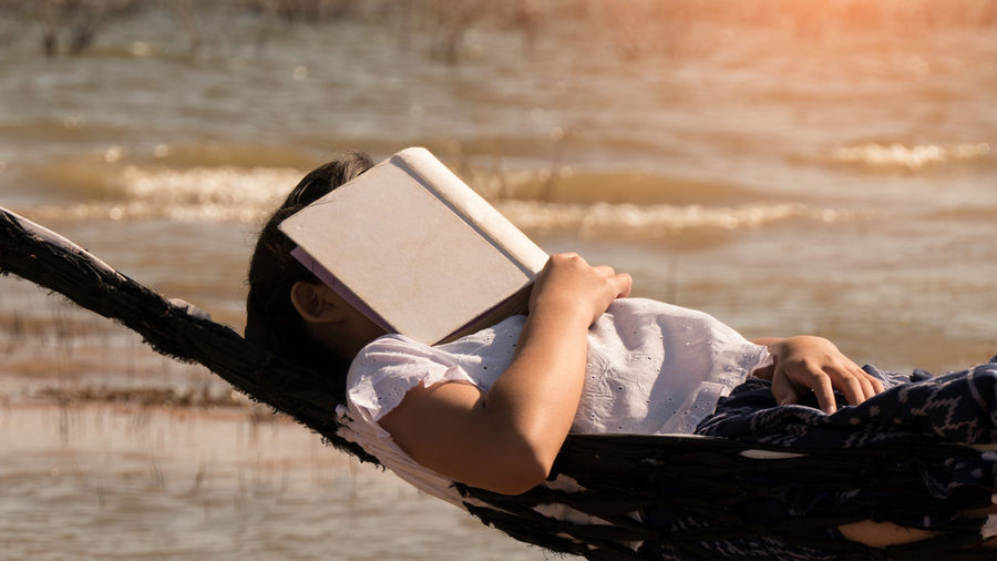 Beach Book Day Focus On Foreground Full Length Land Leisure Activity Lifestyles Lying Down Nature One Person Outdoors Publication Real People Relaxation Sea Sitting Water