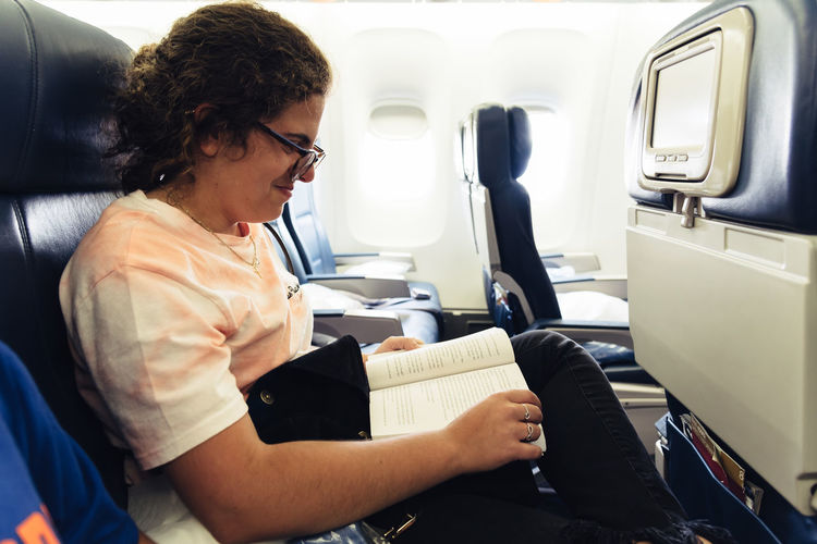 Smiling woman reading book while sitting in airplane