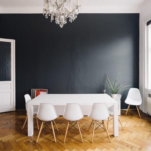 Dining Room Table against Black Wall Dining Room Black Wall Chair Chandalier Day Design Dining Room Table Domestic Room Furniture Hardwood Floor Home Interior Home Showcase Interior Indoors  Inteior Luxury Modern No People Table White Chairs White Chairs And Table White Table