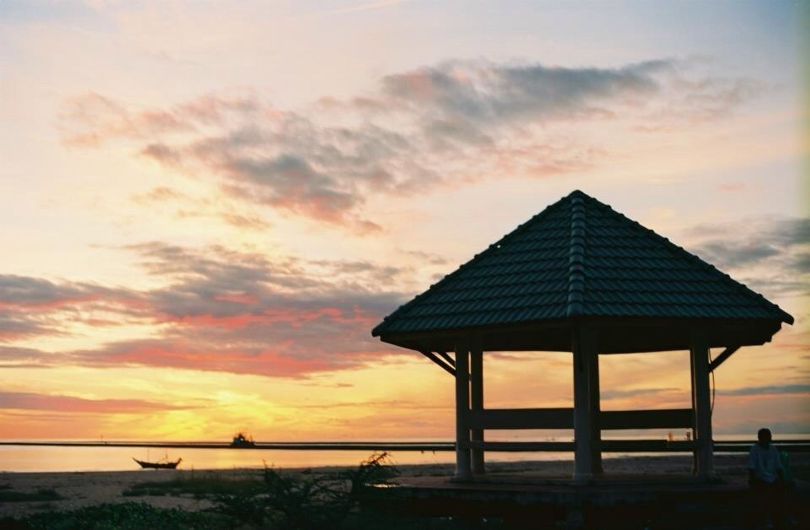 sunset, sky, orange color, sea, scenics, horizon over water, built structure, tranquility, tranquil scene, beach, architecture, beauty in nature, cloud - sky, nature, silhouette, idyllic, cloud, water, building exterior, shore
