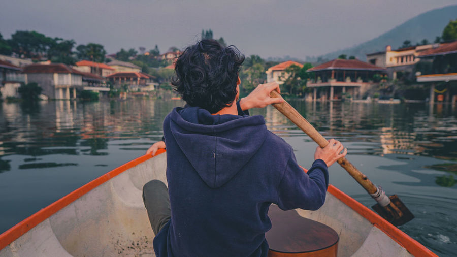 Rear view of man holding boat in river