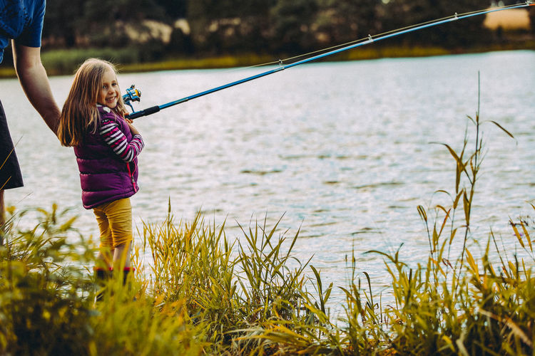 Smiling girl by father fishing in lake