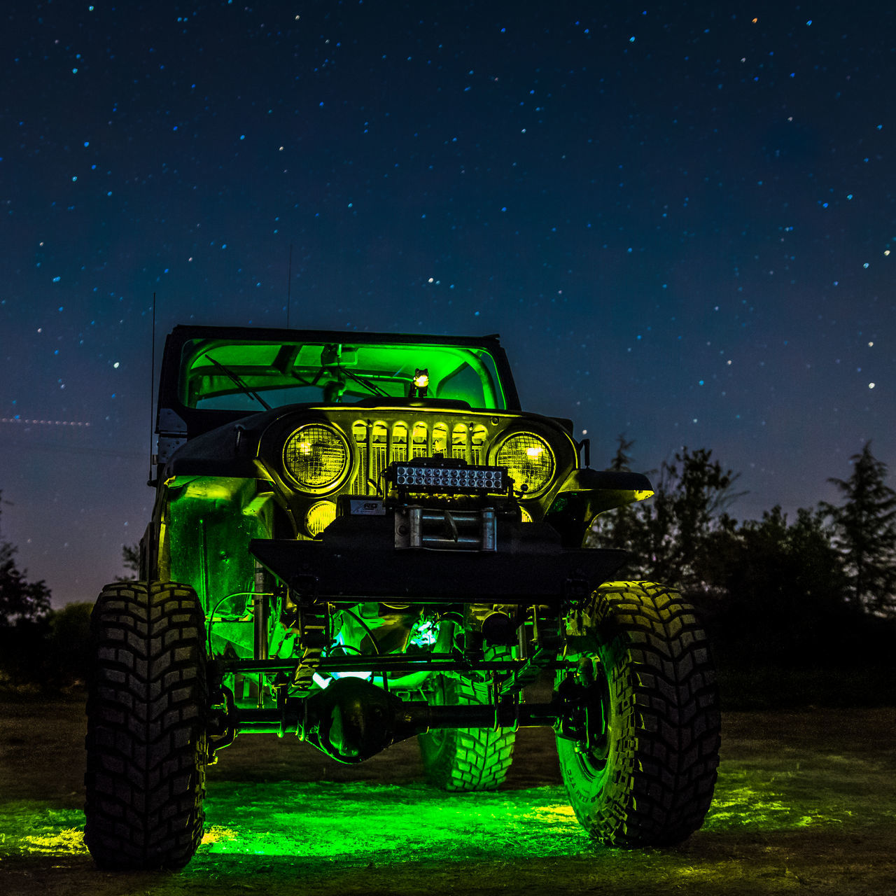 night, transportation, land vehicle, mode of transport, green color, tire, field, low angle view, wheel, 4x4, sky, stationary, astronomy, outdoors, no people, nature, star - space