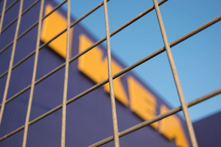 Samut Prakan, Thailand - March 18, 2018 : Exterior of IKEA Store at Mega Bangna , The first branch in Thailand. By taking and focusing on the fence of the building. The background blurred the logo. IKEA Logo Sweden Yellow Flower Blue Clear Sky Close-up Day Decoration Designer  Editorial  Fence Focusing Front Focus Full Frame Furniture No People Outdoors Pattern Self Service Sky Store Yellow