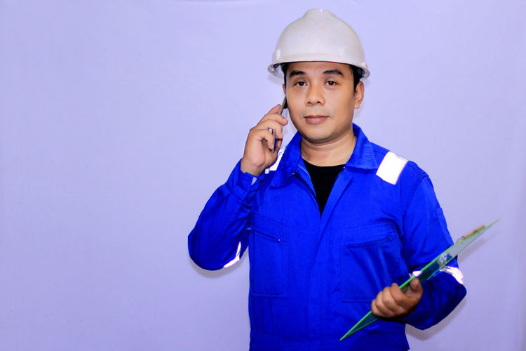 Front View Helmet Looking At Camera One Person Portrait Headwear Hardhat  Holding Standing Hat Protection Blue Construction Industry Occupation Indoors  Safety Copy Space Clothing Real People