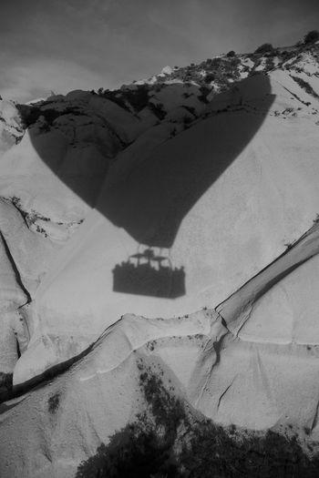 Shadow on hot air balloon on snowcapped mountain