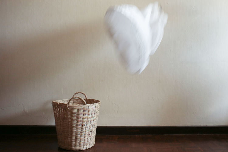 Blurred Motion Of Cloth Above Wicker Basket On Floor At Home