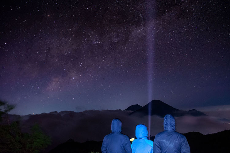 Rear View Of People Wearing Warm Clothing Against Star Field At Night