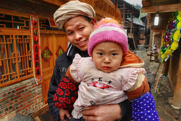 Zengchong village, Guizhou, China - April 13, 2010: The Rural family of Southeast Asia, the father holds the child in her arms, April 13, 2010. Zengchong Dong ethnic minority Village, Guizhou Province, SouthWest China. Rural Family Rural Daughter Positive Emotion Childhood Family Emotion Adult Baby Clothing Child Hat ASIA Chinese People Chinese Village Village Asian  Asiatic; People Chinese China Guizhou,
