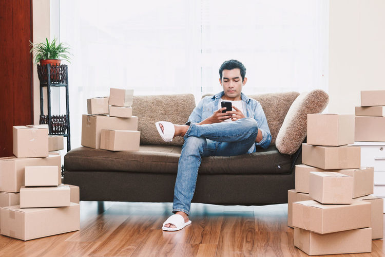 Full length of man using phone while sitting by boxes on sofa at new home