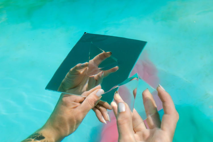 Cropped hand of woman holding pyramid crystal and mirror in swimming pool