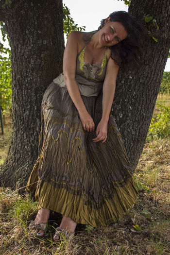 Full length of young woman lying on tree trunk in forest