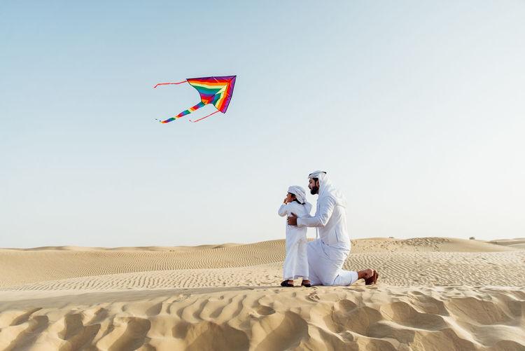 Men standing on desert against clear sky