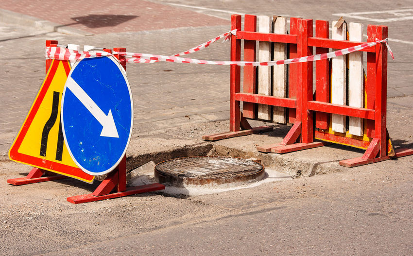 Manhole amid road sign and barrier on street