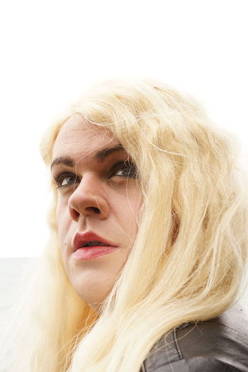 Close-up of transgender male in wig looking away