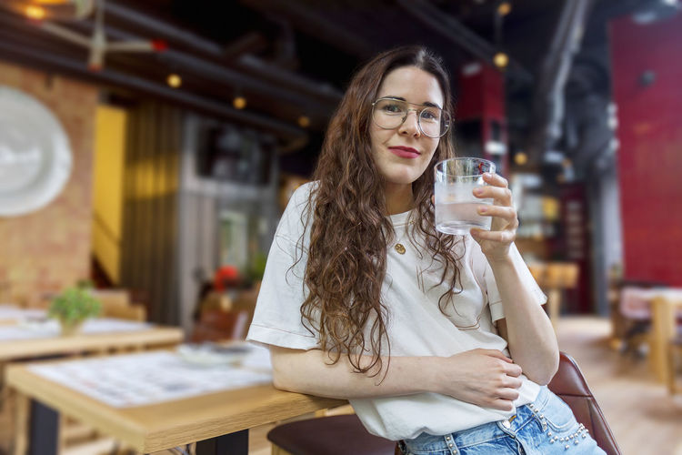 Portrait Of Young Woman Drinking Water At Cafe