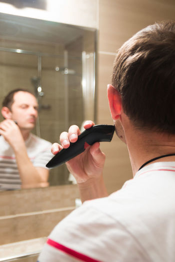 Young man trimming beard in bathroom