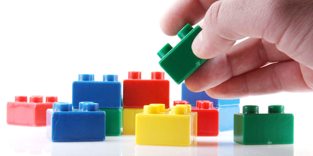 Cropped image of person arranging plastic blocks against white background