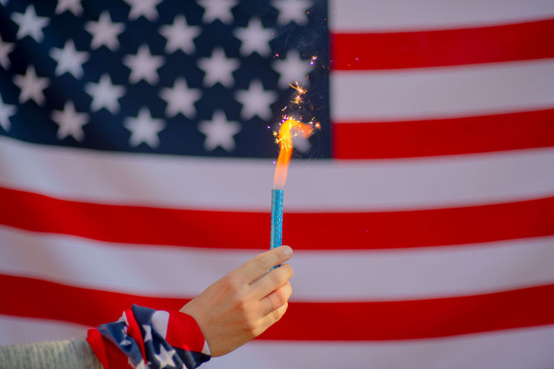 USA flag Red Flag Patriotism Star Shape One Person Striped Human Hand Holding Human Body Part Shape Close-up Burning Indoors  Hand White Color Freedom Independence