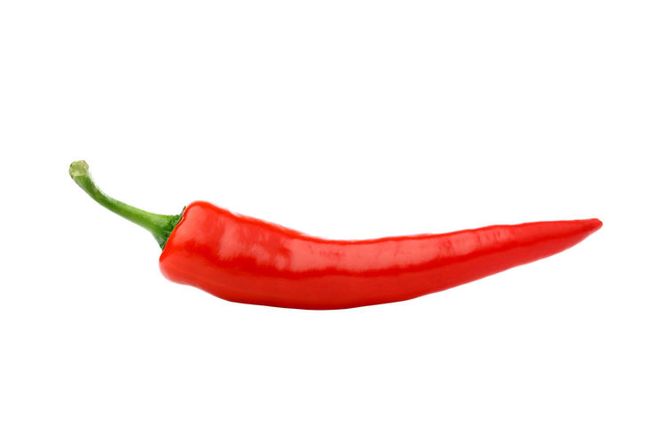 Close-up of red chili peppers against white background
