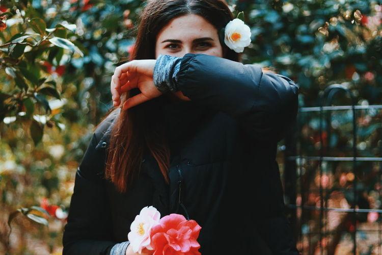 Portrait of woman wearing flower against tree